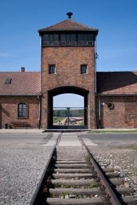 Blick über die Eisenbahngleise auf ein Gebäude der Gedenkstätte Auschwitz.