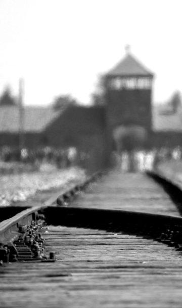Blick über eine Eisenbahnweiche auf markante Gebaeude der heutigen Gedenkstaette Auschwitz