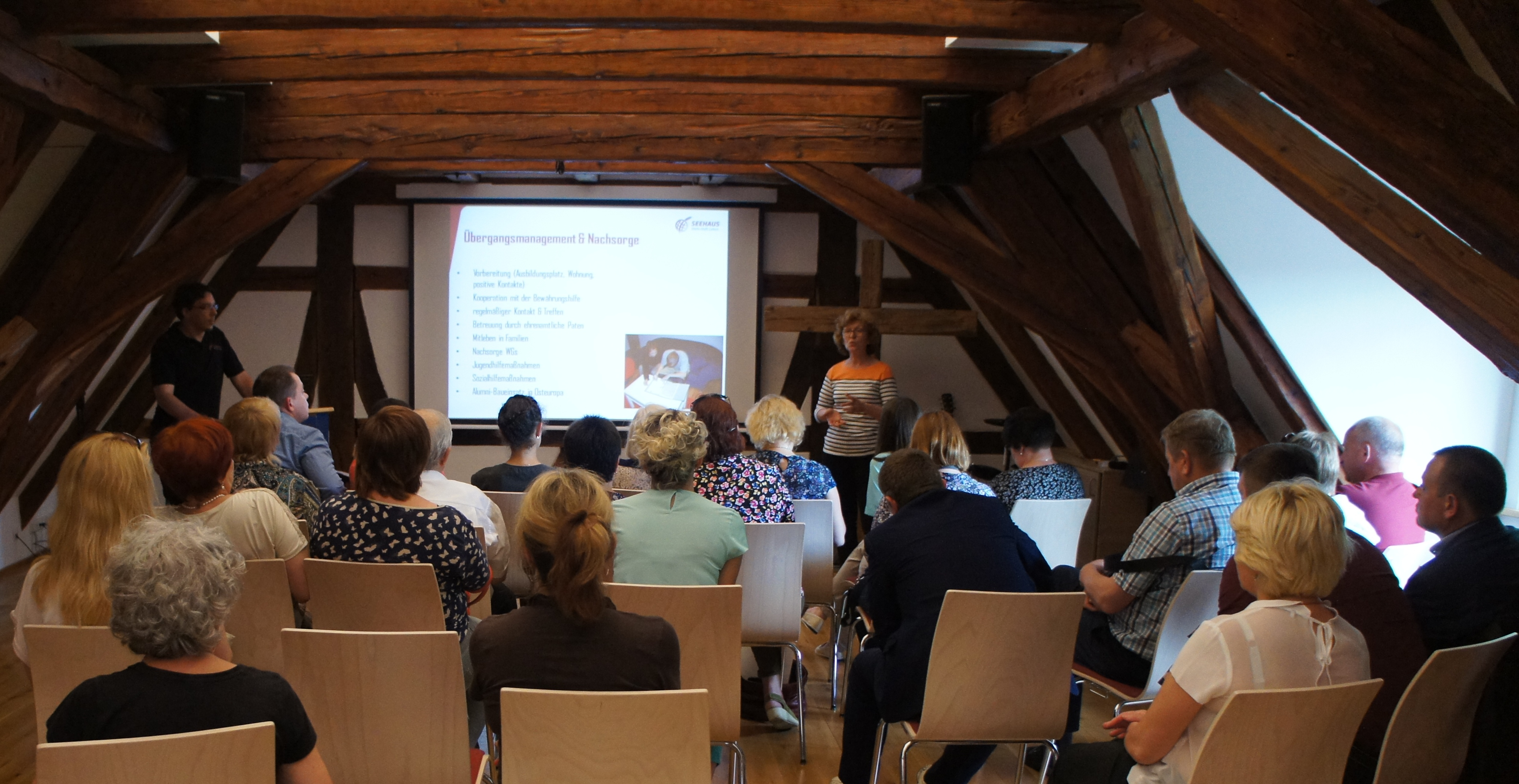 Blick über die Köpfe des Publikums auf die Präsentation auf dem Dachboden.