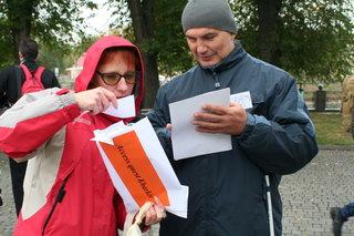 Dieses Foto zeigt zwei Helfer der Geschichtswerkstatt Tschernobyl  in Charkiw, die sich gerade mit Wegweisern und anderen Papieren beschäftigen.