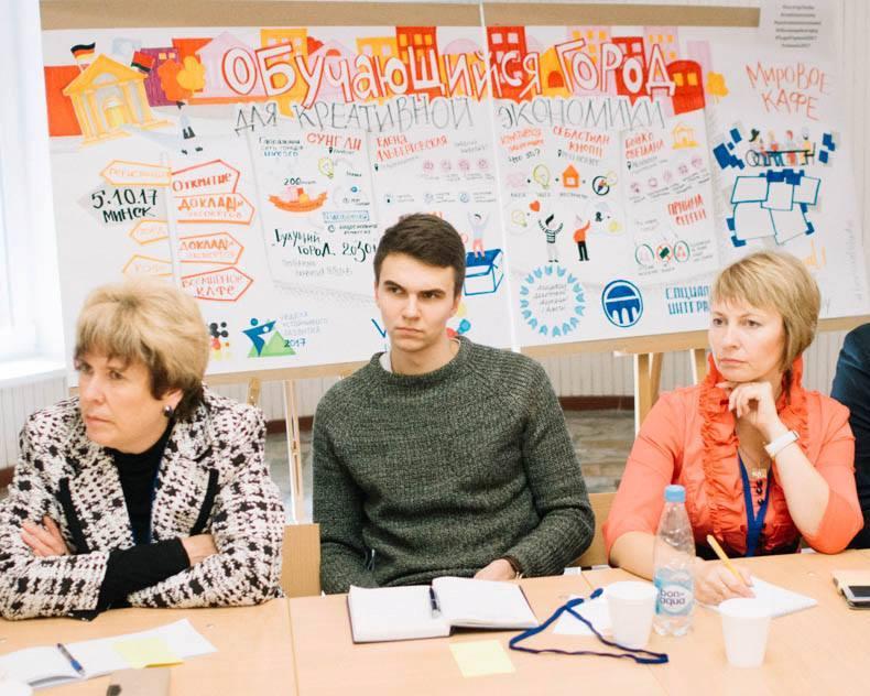Unser Foto zeigt drei Zuhörerinnen und Zuhörer vor einem bunt gestalteten Wandbild.