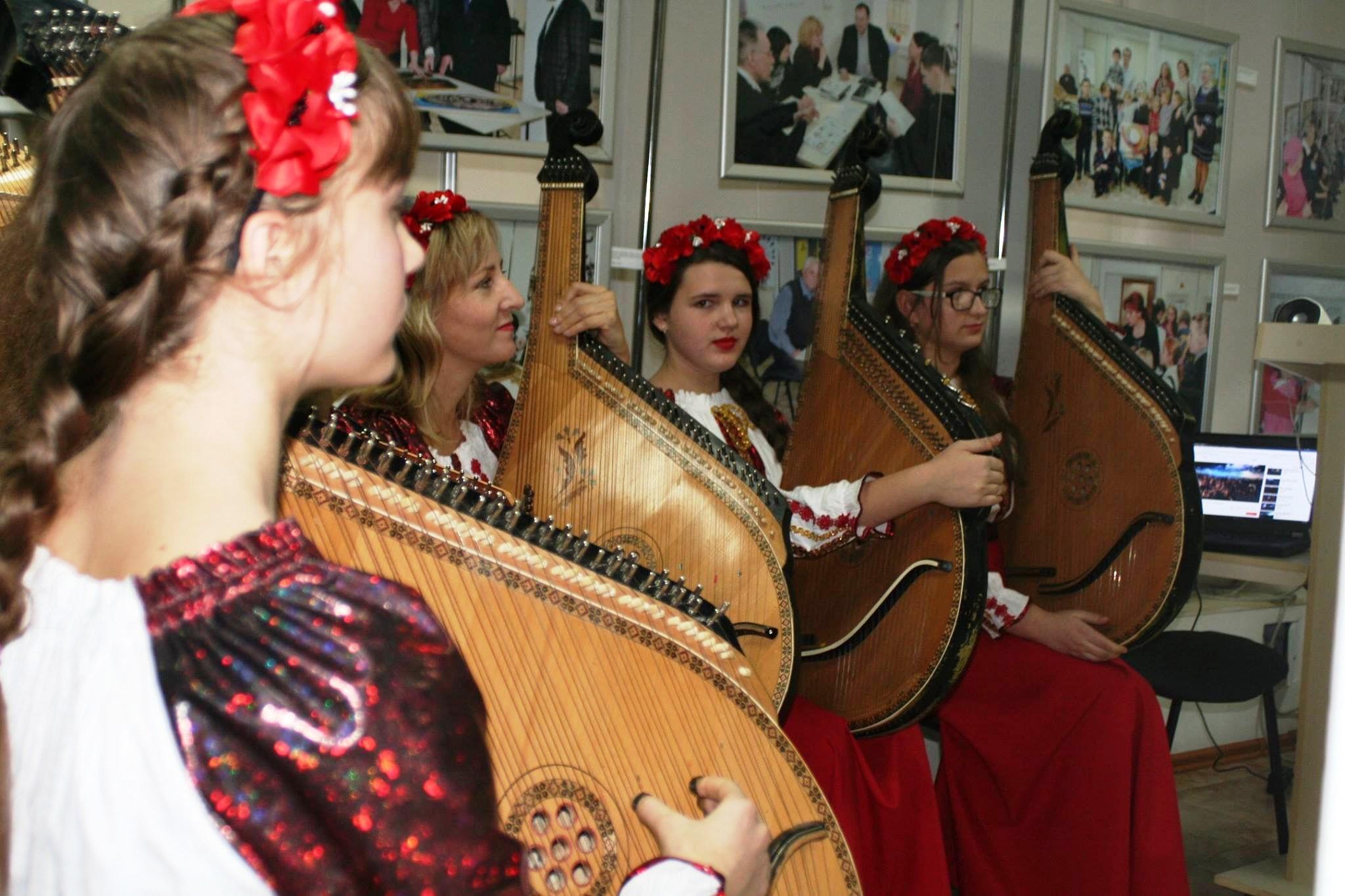 Unser Foto zeigt die fünf junge Musikerinnen, die traditionelle ukrainische Saiteninstrumente spielen, in der Geschichtswerkstatt Charkiw.