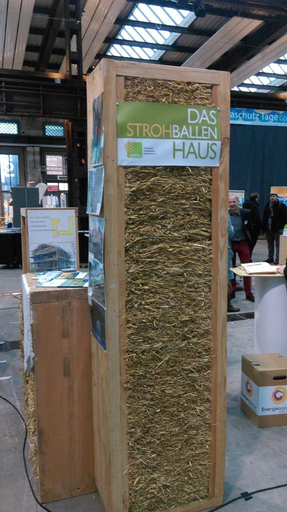 Das Foto zeigt einen Querschnitt durch die Wand eines Strohballenhauses. Die Bauarbeit dient der Energieeffizienz und Nachhaltigkeit.
