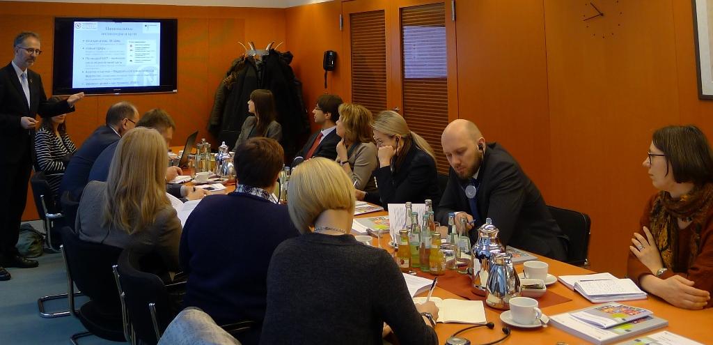 Das Foto zeigt die Delegation aus Belarus in einer Seminarsituation in einem Raum im Bundeskanzleramt in Berlin.