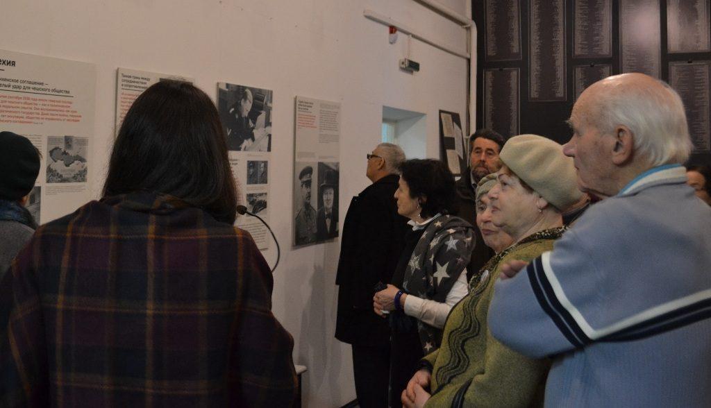 """Unser Foto zeigt Erwachsene beim Blick auf die Ausstellung """"Different Wars""""am internationalen Holocaust-Gedenktag 2018 in der Geschichtswerkstatt."""