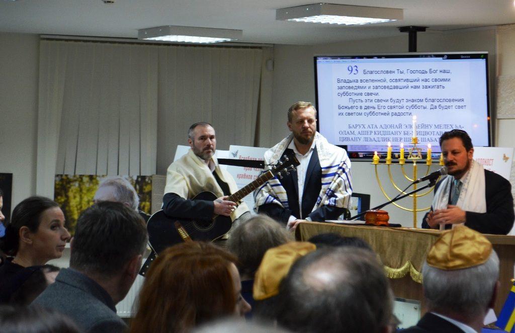 Dieses Foto zeigt den Rabbi und zwei Musiker mit Gitarren hinter einer Menora mit sieben Kerzen am internationalen Holocaust-Gedenktag.