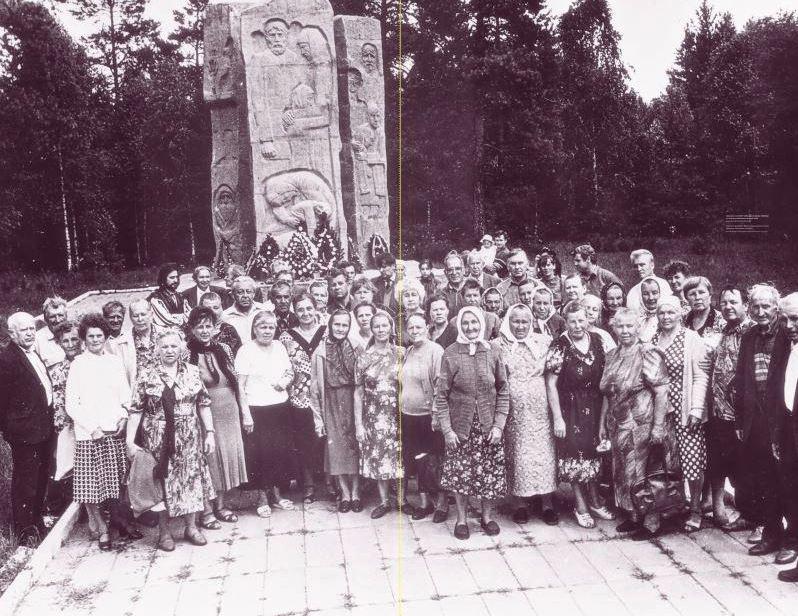 """Dieses Foto zeigt etwa 60 ältere Menschen vor einem Gedenkstein, der an das Todeslager Osaritschi erinnert. Die Erinnerung an das Todeslager Osaritschi ist unter anderem mit diesem Foto nun Teil der Wanderausstellung """"Vernichtungsort Malyj Trostenez. Geschichte und Erinnerung"""". Das Denkmal wurde erst 194 errichtet. Das Foto entstand bei einem Treffen ehemaliger Häftlinge am 3. Juli 1997. Foto: Museum des Großen Vaterländischen Krieges Minsk"""