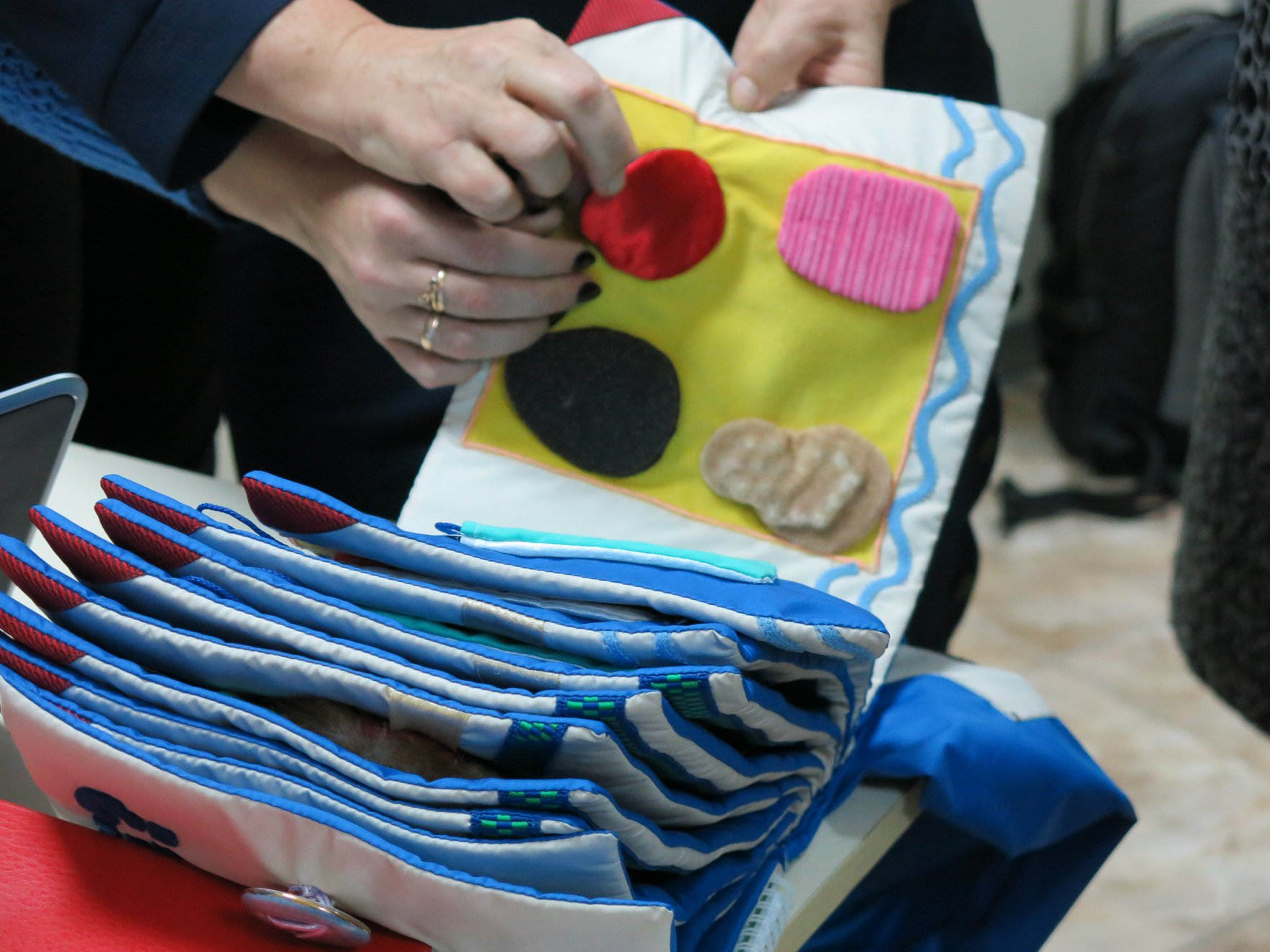 Unser Foto zeigt ein Tastbuch, das unterschiedliche Materialien zum fühlenden erkunden anbietet.