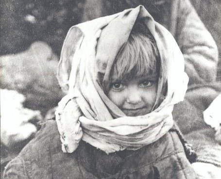 Das historische Schwarz-Weiß-Foto zeigt ein Kind, das schüchtern und glücklich in die Kamera lächelt. Aufgenommen wurde das Foto von sowjetische Armee-Fotografen. Sie hatten die Überlebenden des Todeslagers Osaritschi fotografiert.