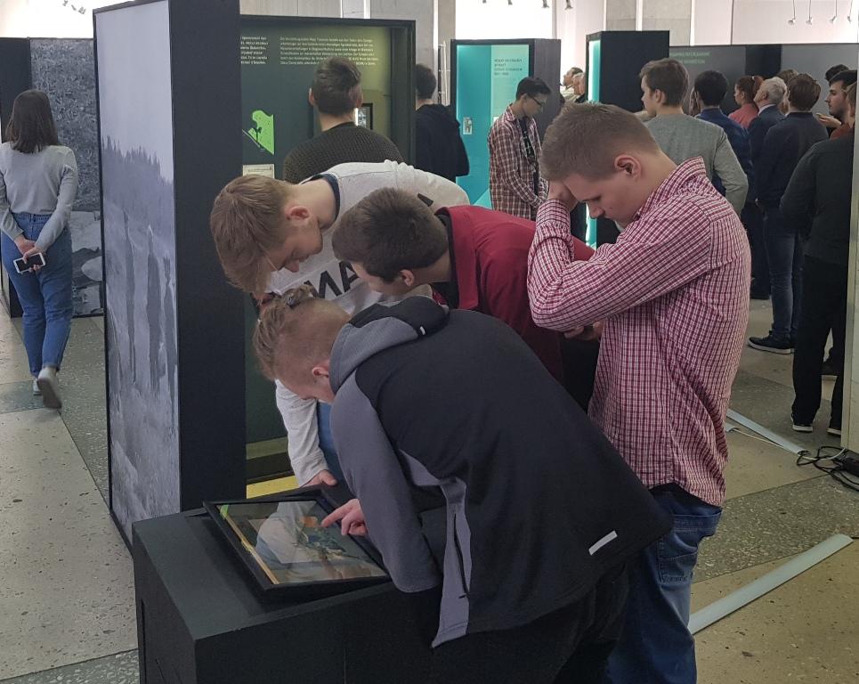 Die Inhalte der Ausstellung werden auch interaktiv erkundet. Dieses Foto zeigt Jugendliche an einem interaktiven Modul der Ausstellung.