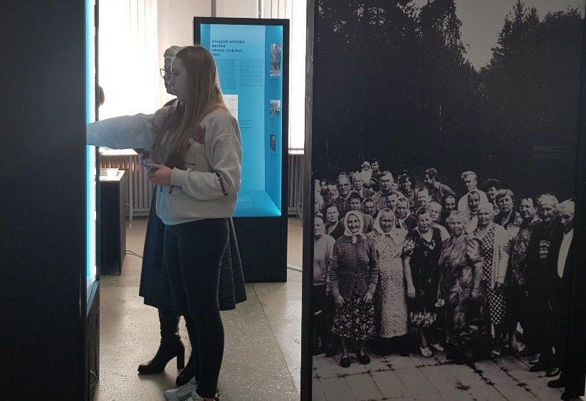 """Erst seit wenigen Wochen gehören die Module über das Todeslager Osaritschi zur Wanderausstellung """"Vernichtungsort Malyj Trostenez. Geschichte und Erinnerung"""". Dieses Foto zeigt eine der Tafeln und zwei Besucherinnen."""