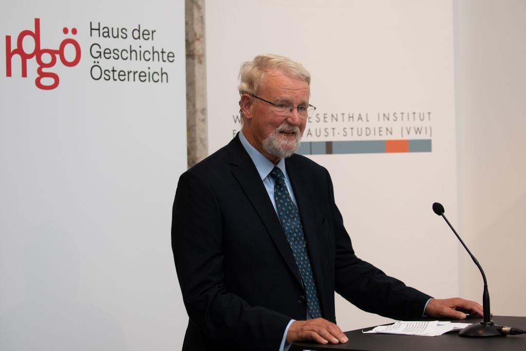 """Matthias C. Tümpel, Vorsitzender des IBB e.V., am Rednerpult bei der Eröffnung der Wanderausstellung """"Vernichtungsort Malyj Trostenez. Geschichte und Erinnerung"""" in Wien."""