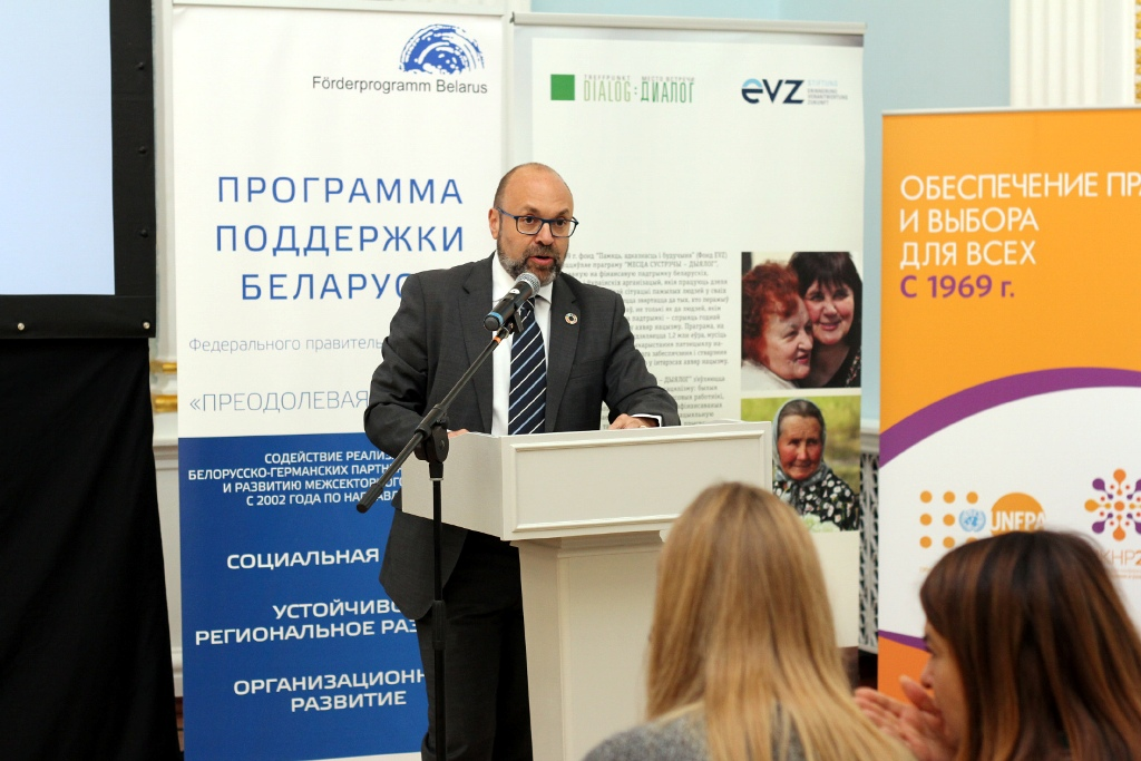 Jaime Nadal, Repräsentant des UNFPA, bei seiner Ansprache in Minsk am Rednerpult vor einem Aufsteller Förderprogramm Belarus.
