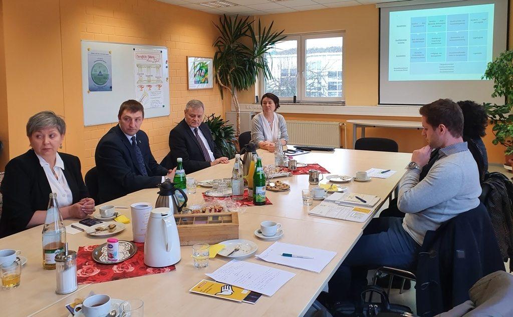 Dieses Foto zeigt die Delegation, die ím Rahmen des Förderprogramms Belarus die Stadt Bonn besichtigt hat, bei einer Diskussionsrunde in den Gemeinnützigen Werkstätten.